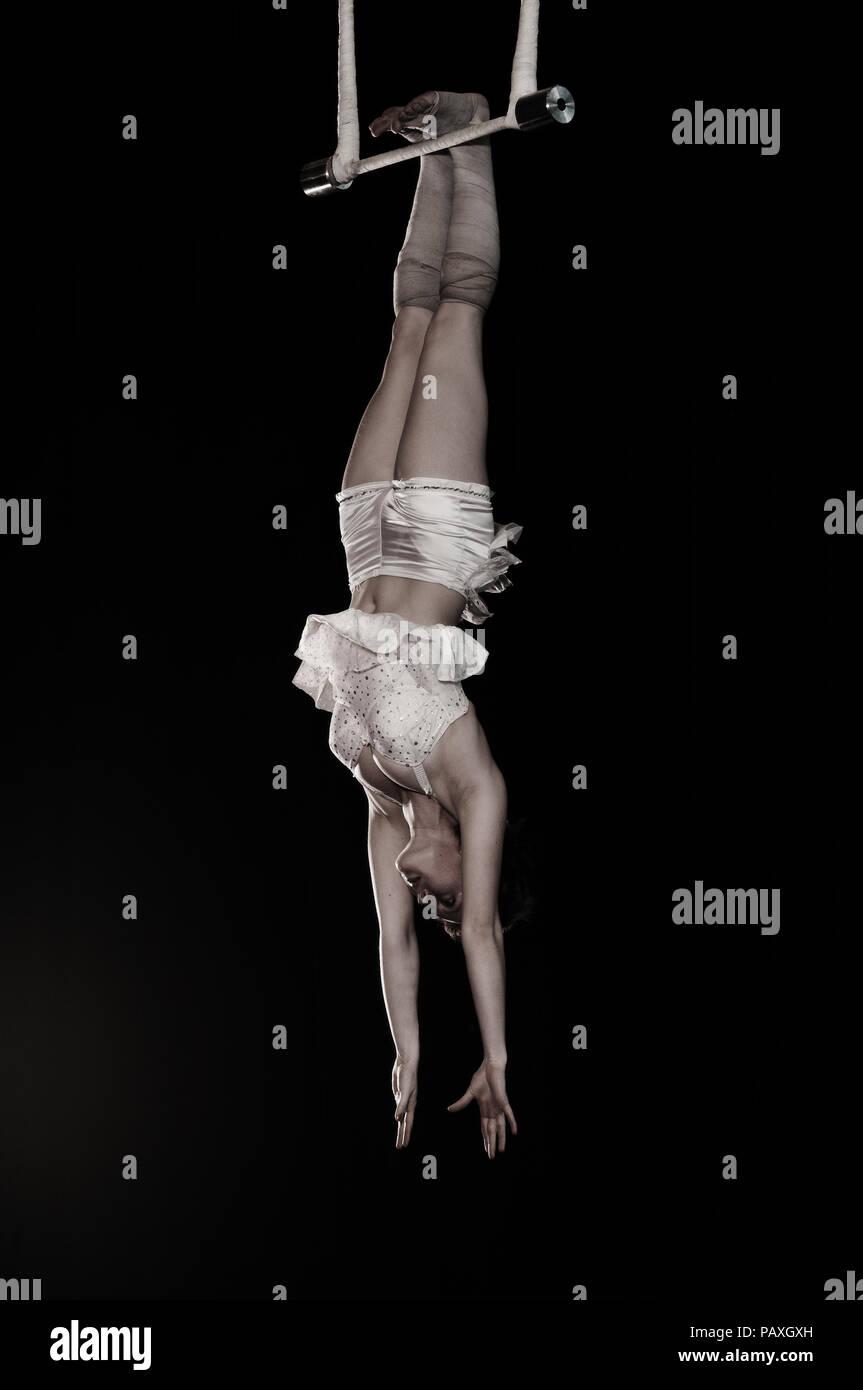 Carly est une trapéziste suspendu à ses pieds. Les élèves de l'Institut National des Arts du Cirque ont des talents exceptionnels. Banque D'Images