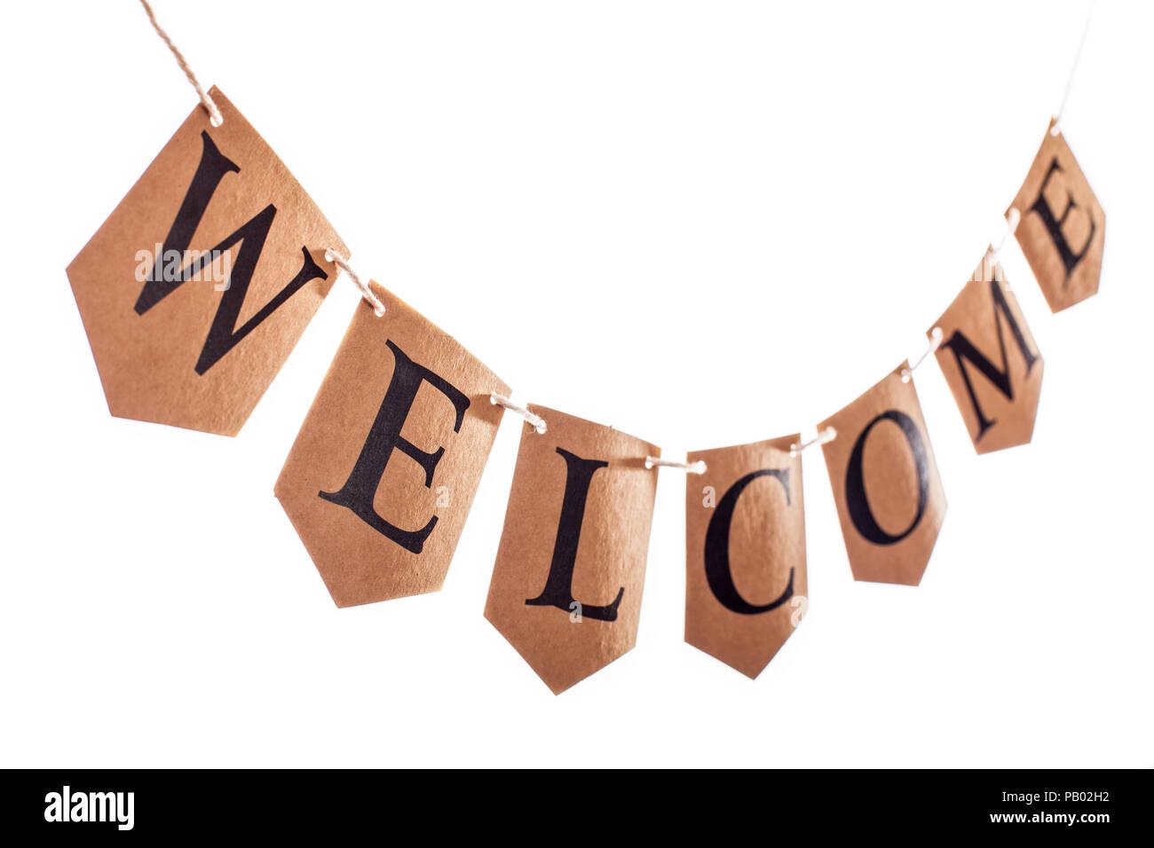 Bannière de bienvenue. Texte Bienvenue sur pendaison bunting dans focus sélectif contre fond blanc. Le mot orthographié Bienvenue sur carte marron lettres. Page d'accueil Photo Stock