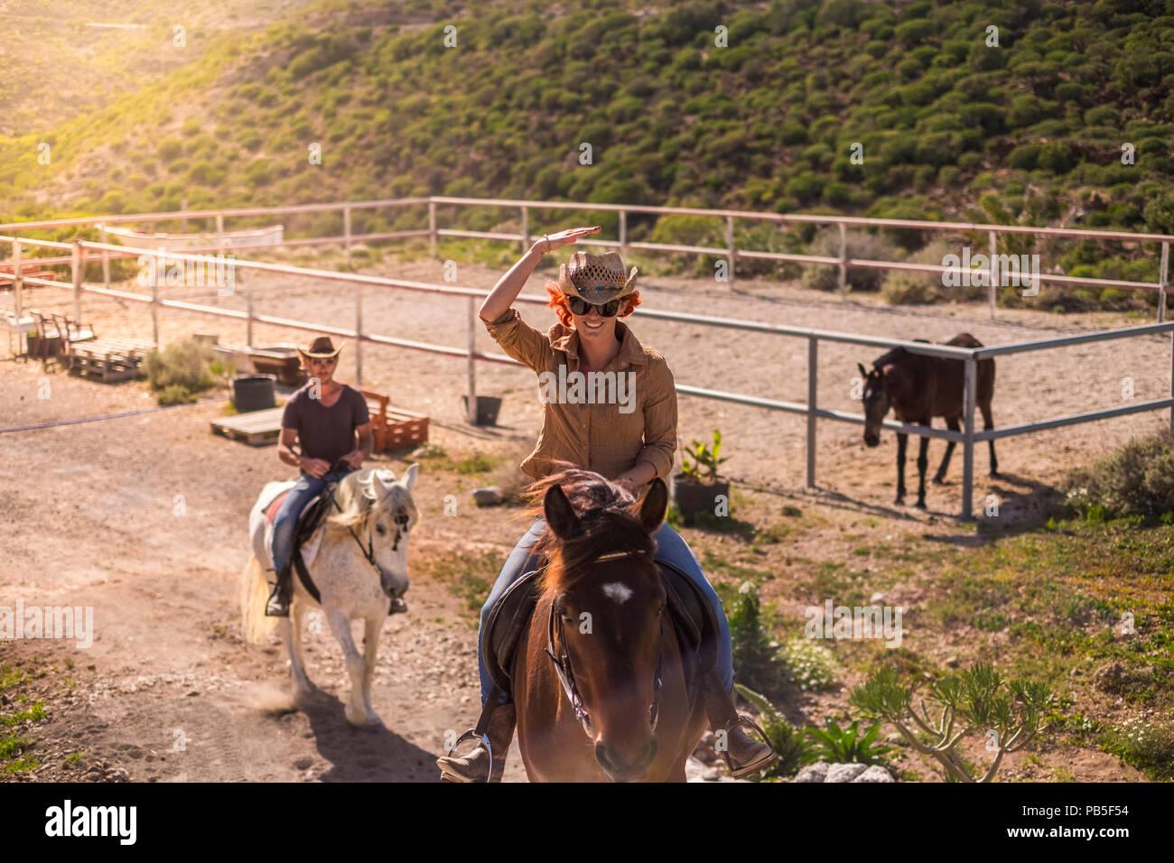 Couple de rider l'homme et la femme avec Brown et chevaux blancs rendez-vous et profitez de la piscine en plein air activité de loisirs dans les montagnes voyage excursion cowbo moderne. Photo Stock