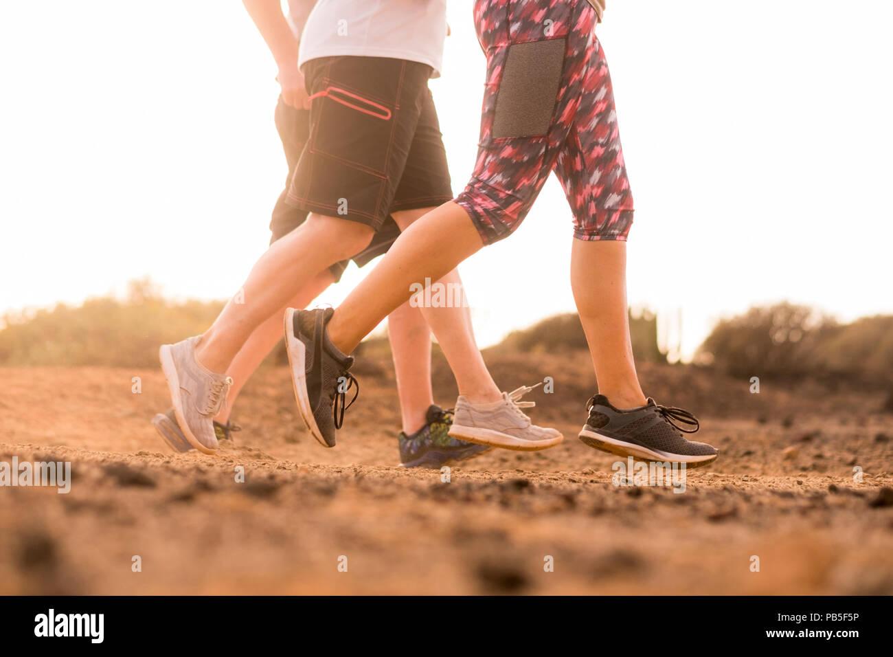 Groupe de trois caucasian runner doing jogging sur le sol du désert de l'activité en plein air dans la nature. Sport et mode de vie sain pour les gens de l'été soleil météo. Photo Stock