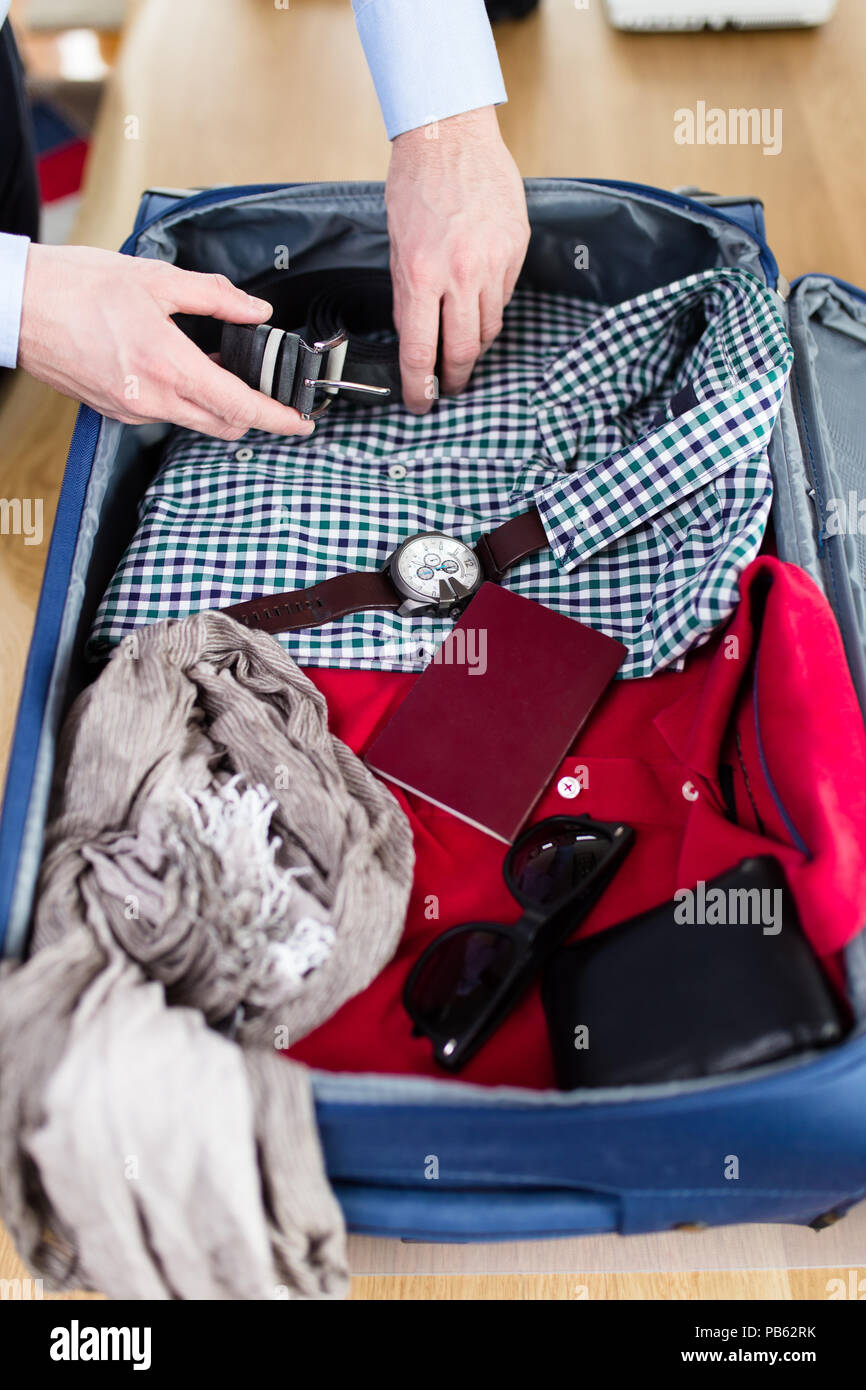 La préparation de l'homme pour les affaires en voyage. Ouvrir le sac du voyageur avec passeport, vêtements et accessoires. Voyage et vacances concept. Photo Stock