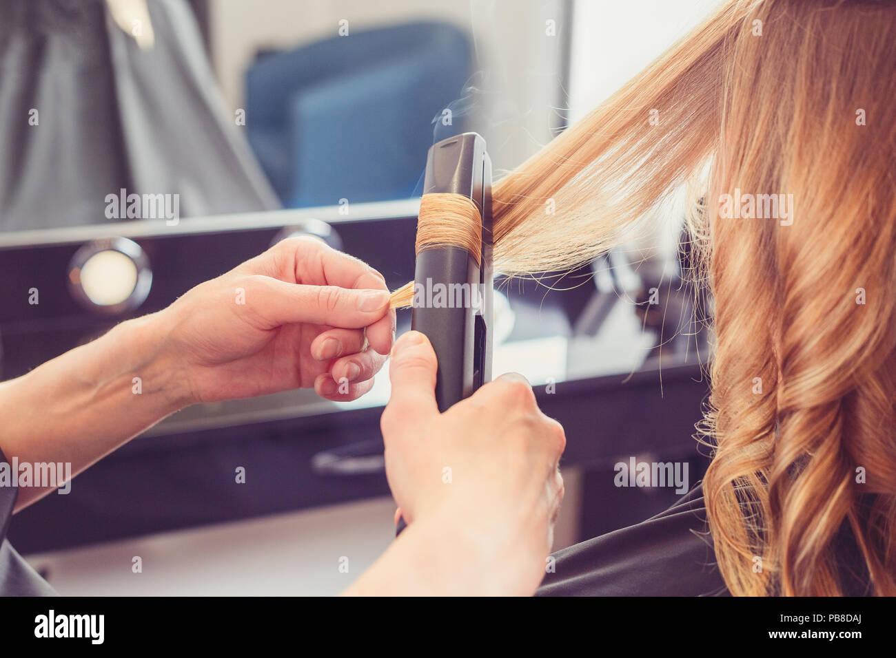 Coiffure coiffure pour un client avec un fer à friser en instituts de beauté Photo Stock