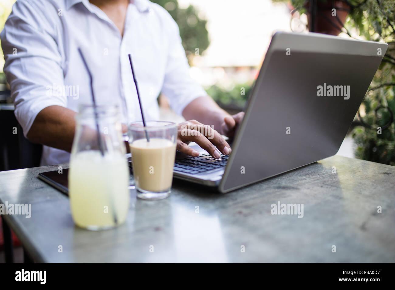 Les jeunes afro-américains attractive businessman sitting in cafe bar, boire du café et avoir fait quelques travaux sur ordinateur portable. Photo Stock