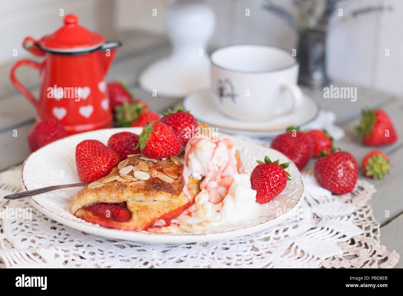 Des pâtisseries sucrées pour le petit-déjeuner. Avec le remplissage de fraises et de la crème glacée. Le café du matin. Pot à lait rouge. laitier. Une tasse de thé. petit déjeuner en famille. Photo en couleurs blanc Photo Stock