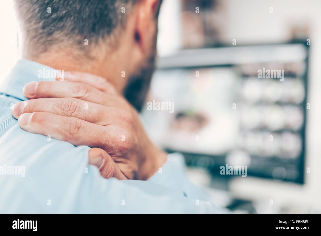 Employée de bureau avec le cou et la douleur dorsale de siéger au bureau toute la journée Photo Stock