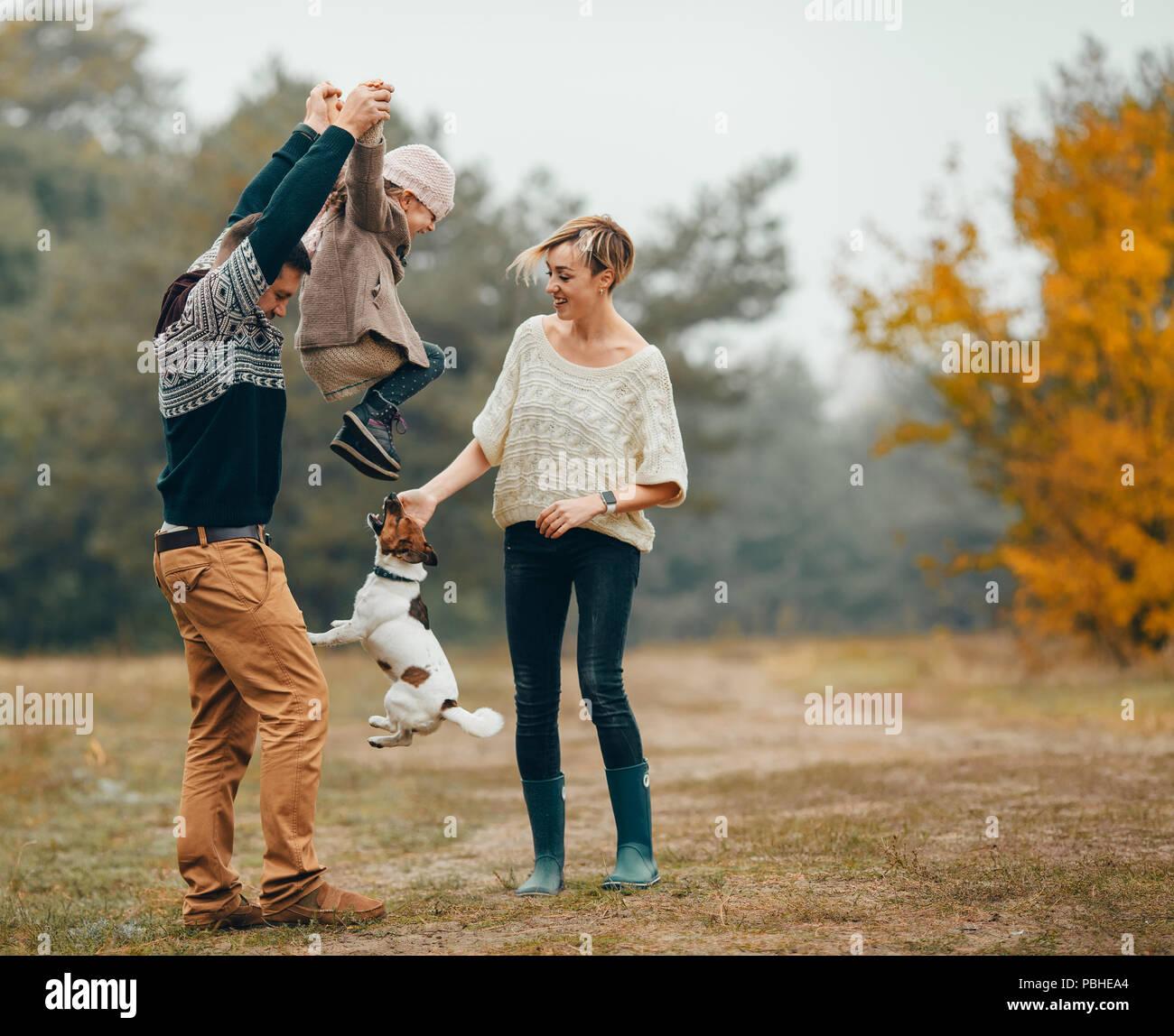 Heureux parents s'amuser et élèvent leur fille au chemin forestier en regard de chien sautant au cours de marche en forêt d'automne. Banque D'Images