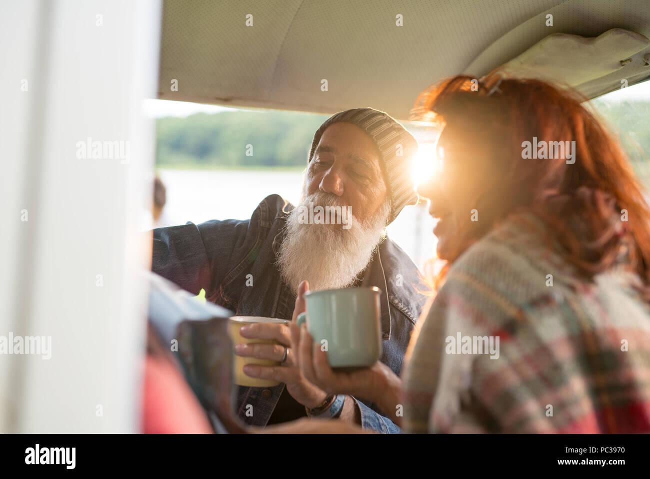Vieux couple hipster assise dans une voiture et à la recherche à une carte routière Photo Stock