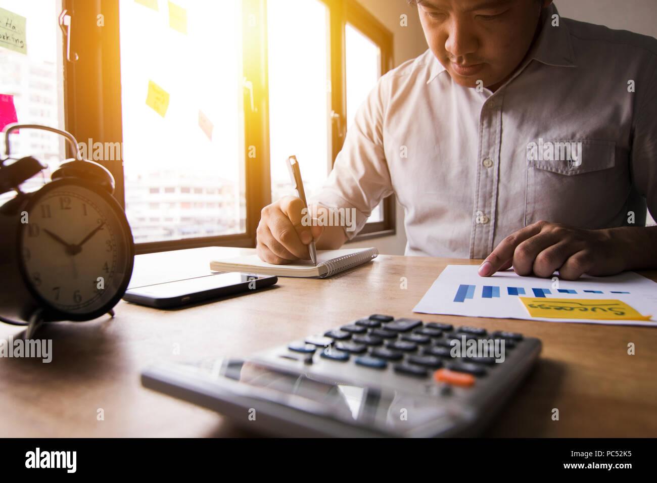 Calculer comptable finances des bénéfices annuels par appuyer sur la calculatrice et résumer l'équilibre de l'argent en écrivant sur la note book in office Photo Stock