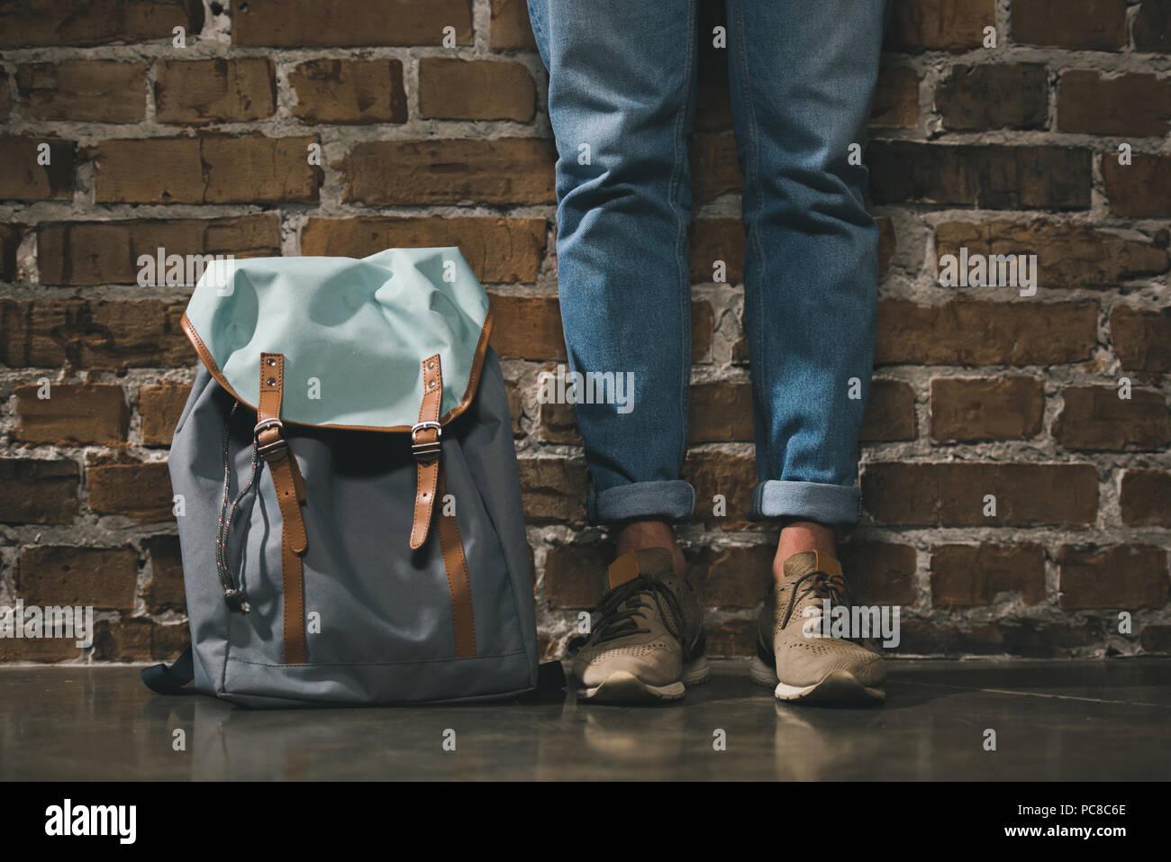 La section inférieure de l'homme en pantalon en jean et baskets debout avec sac à dos près de brick wall Photo Stock