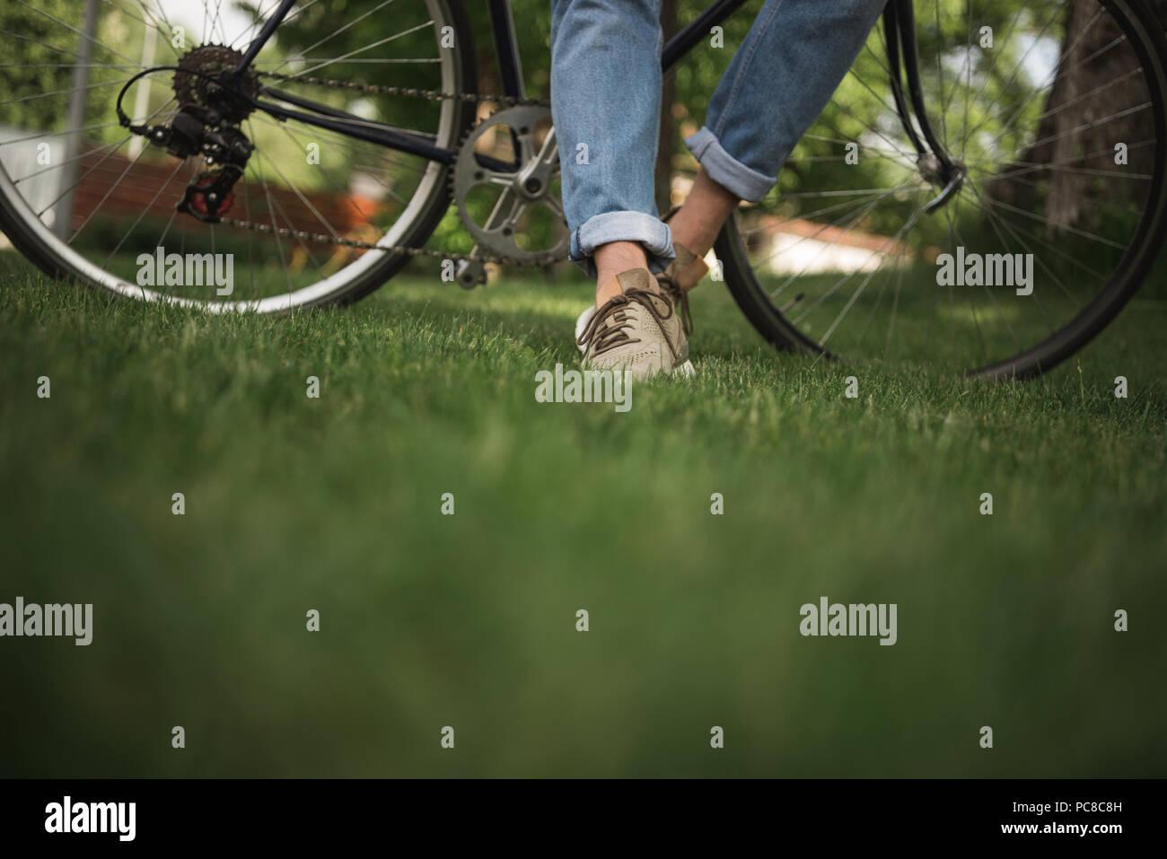 La section inférieure de l'homme en jeans avec permanent location on Green grass Photo Stock