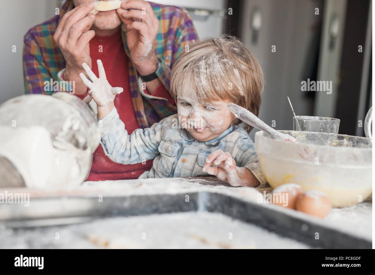 Le père et l'enfant s'amusant avec de la farine de cuisine Photo Stock