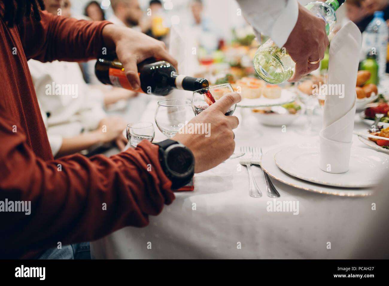 Un homme se verse dans un verre de vin rouge Banque D'Images