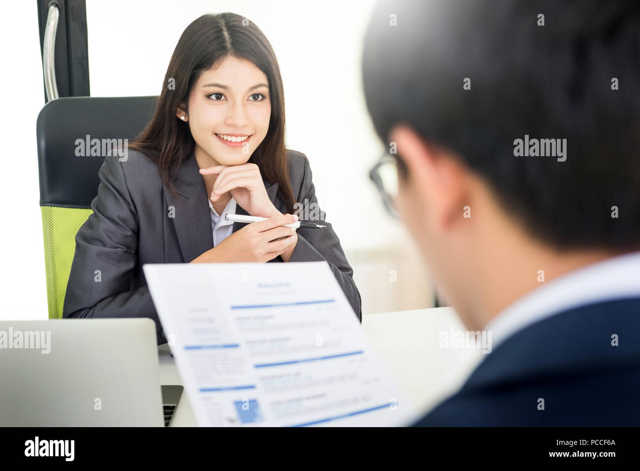 Femme Manager mener une entrevue d'emploi avec candidate à un air narquois avec son CV dans sa main et parler à son subordonné à l'h Photo Stock