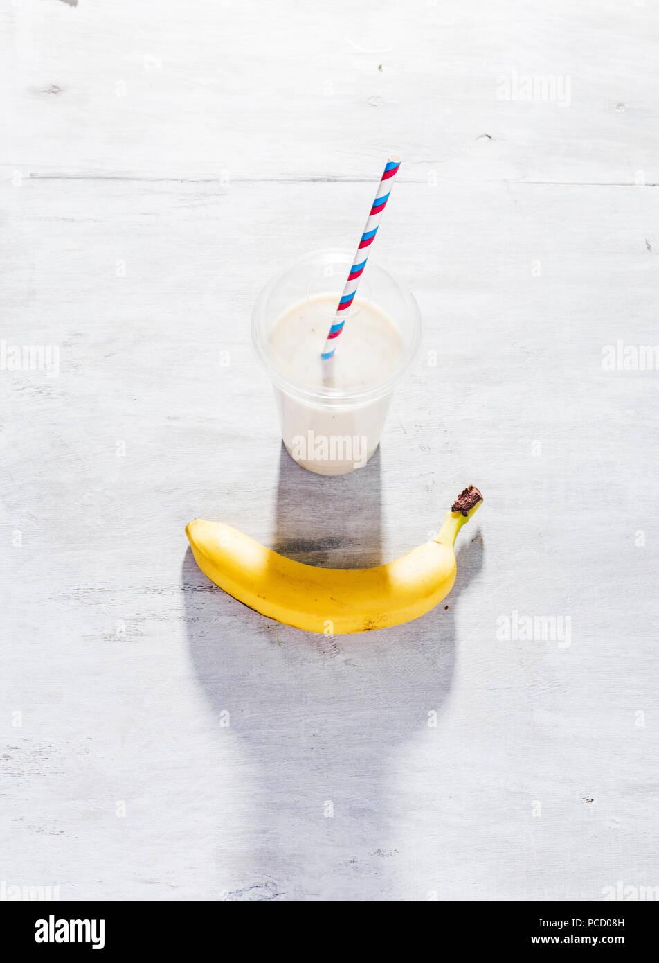 Milkshake banane dans la tasse en plastique sur la table en bois blanc Photo Stock