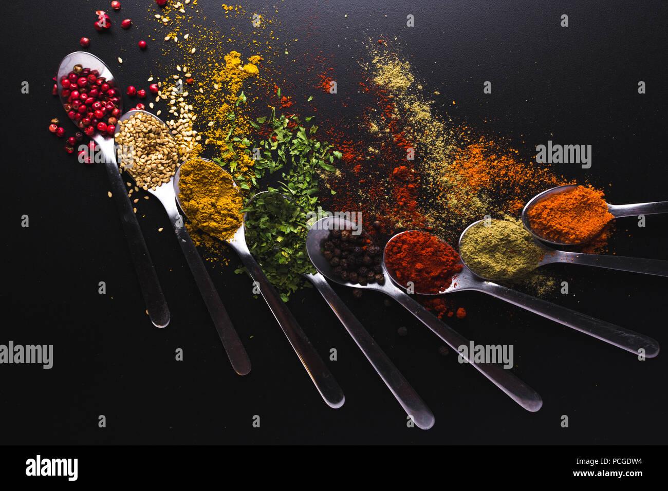 Composition de petites cuillères plein d'épices et de condiments pour la cuisine sur un fond noir Photo Stock
