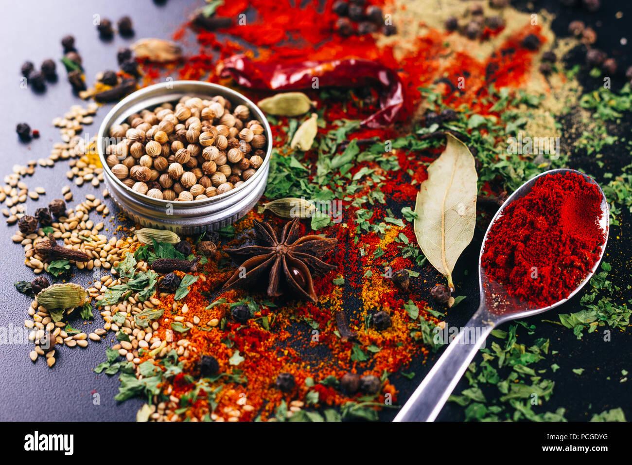 Catastrophe d'épices et de condiments pour la cuisine, sur un tableau sombre, concept de restaurant Photo Stock