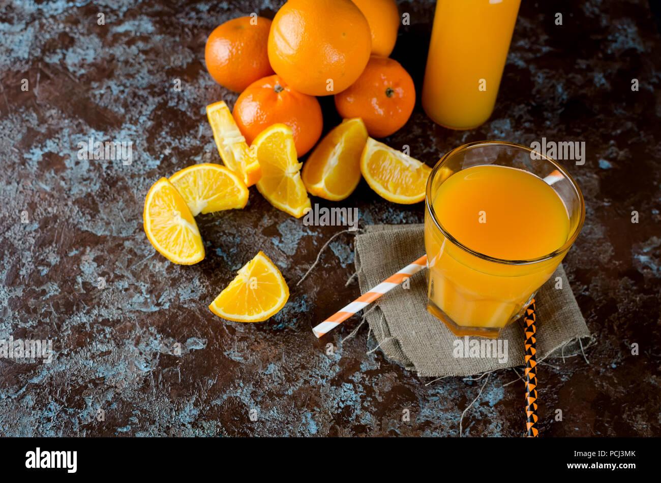 Le jus d'orange dans un verre et une bouteille et des morceaux d'orange sur un fond bleu-brun copy space Photo Stock