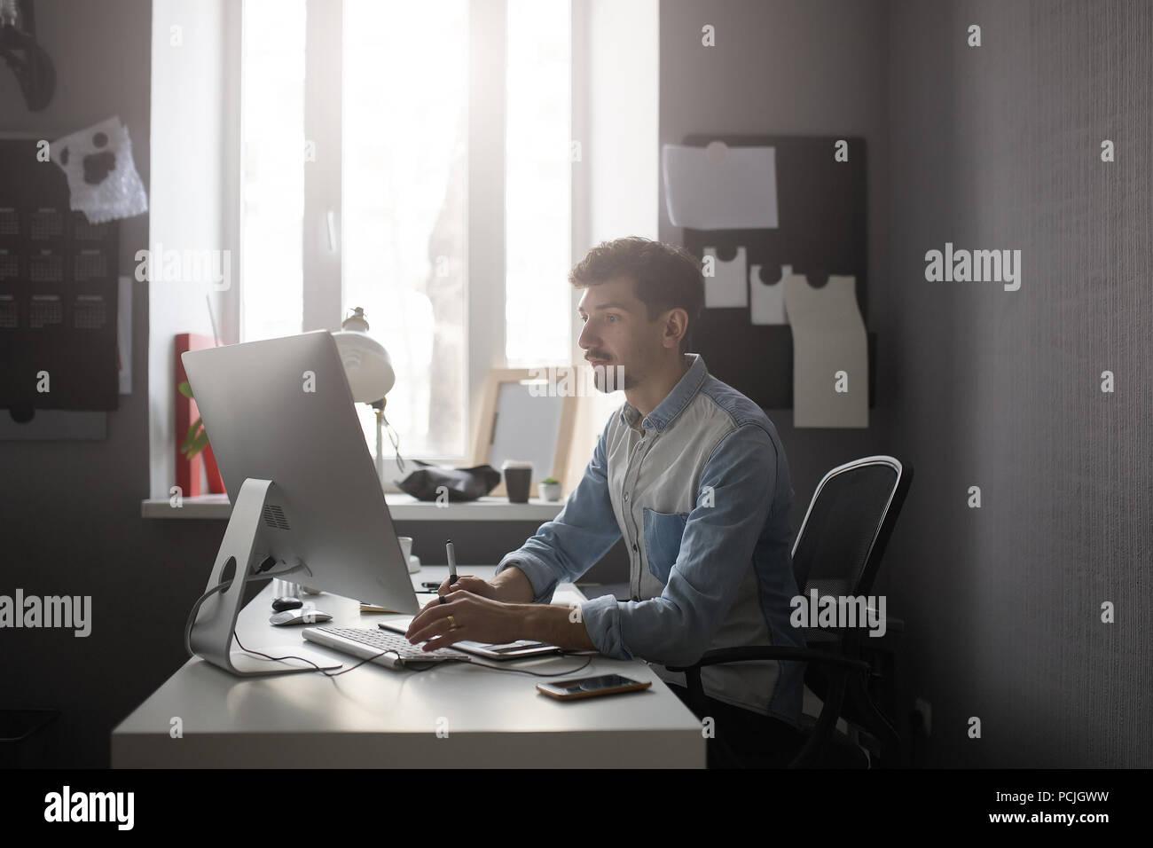 Jeune mâle concepteur à l'aide de tablette graphique tout en travaillant avec com Photo Stock