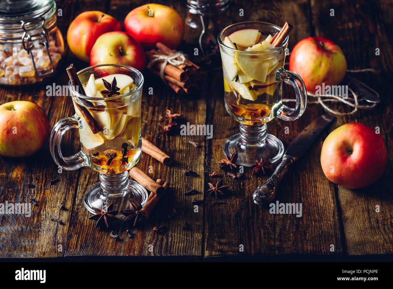 Verres de boisson épicée Apple avec girofle, cannelle, l'étoile d'anis et de sucre candy. Tous les ingrédients et quelques ustensiles de cuisine sur table en bois. Vertic Photo Stock