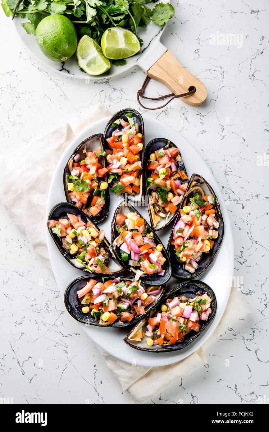 La nourriture péruvienne. Choros a la chalaca. Gros moules, choros zapatos assaisonné de purple oignon, les tomates, le maïs et le citron. Vue de dessus, fond blanc. Plat péruvien traditionnel Photo Stock