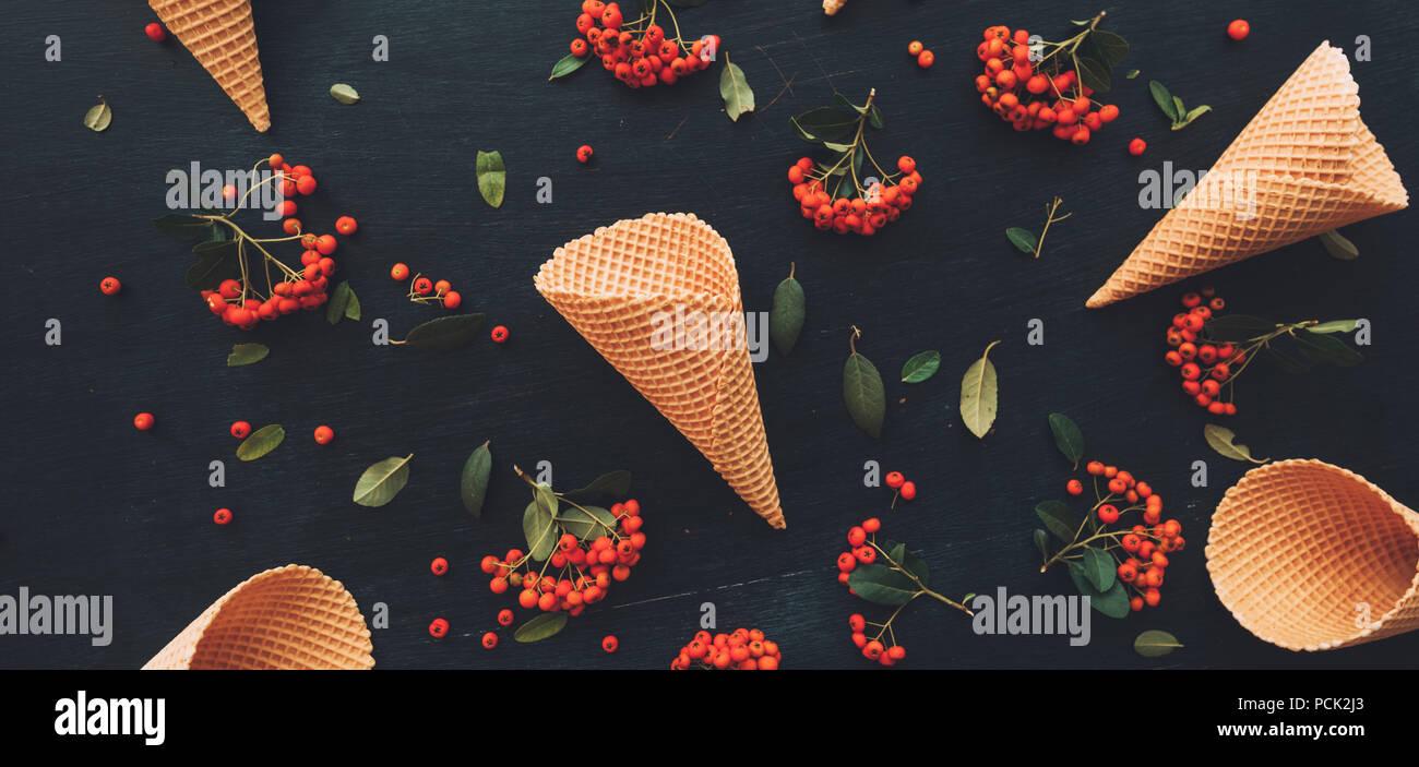 Waffle ice cream cone télévision jeter dessus noir foncé sur fond de bois décoré de petits fruits sauvages arrangement Photo Stock