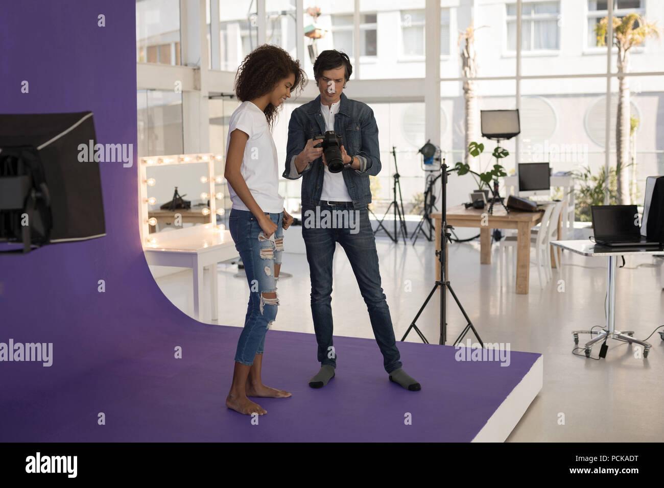 Photos de photographe montrant fashion model sur appareil photo numérique Photo Stock