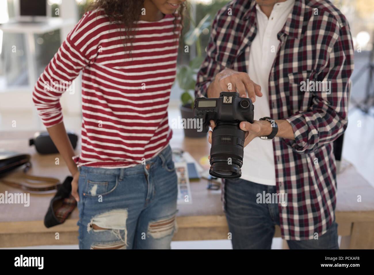 Photographe de mode pour des photos montrant le modèle de caméra numérique en studio Photo Stock