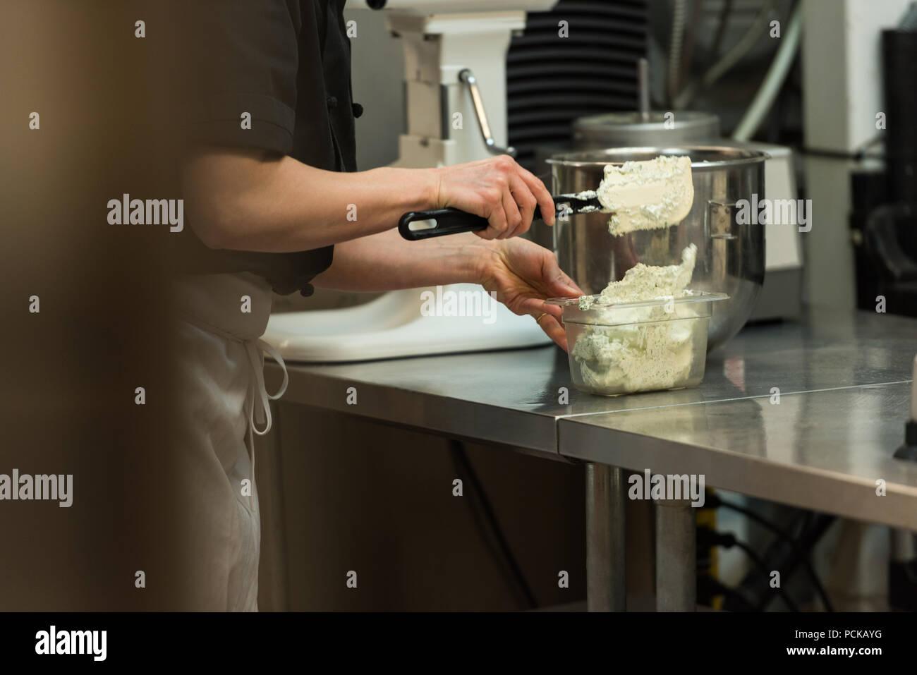 Chef putting la crème fouettée dans le récipient Photo Stock