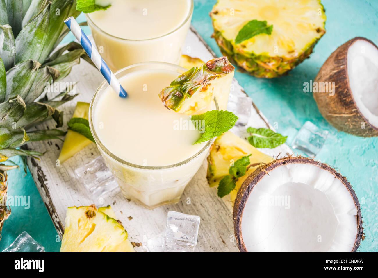 Boisson d'été rafraîchissante, de pina colada cocktail, sur un fond bleu clair, avec des morceaux d'ananas, noix de coco, de glace et de feuilles de menthe, copy space Banque D'Images