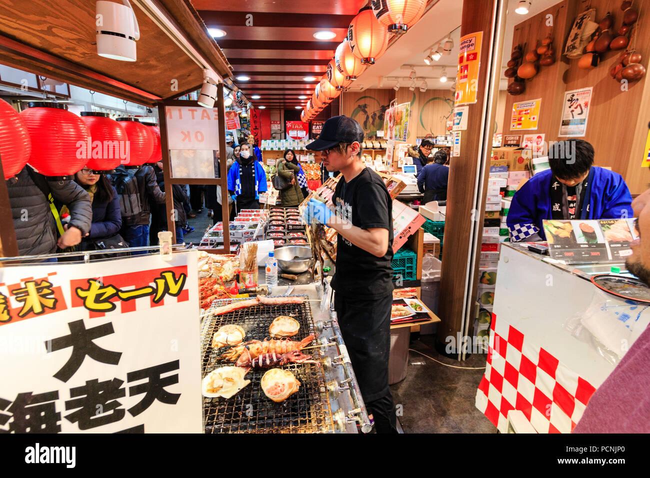 Kuromon Ichiba, marché alimentaire à Osaka. Des marchands de poisson magasin vendant des emballages, des fruits de mer et poissons cuits en-cas. L'homme déchire les jambes de crabe Photo Stock