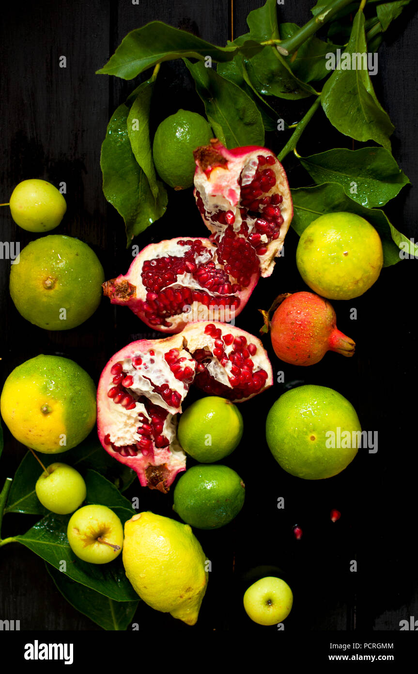 Citron sur une branche et les limes. grenade haché. sur un fond noir. photo sombre. gouttes d'eau. fruits humides Photo Stock