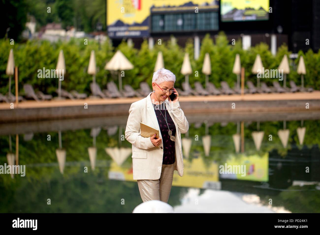 Cheerful businesswoman appelant sur téléphone mobile app tout en vous reposant à l'hôtel Photo Stock