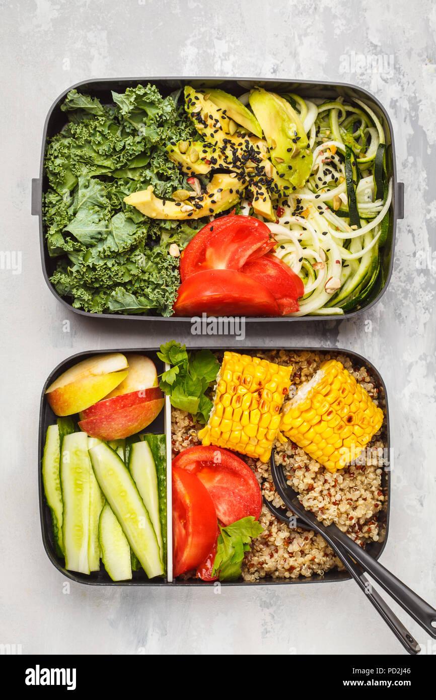 Préparation des repas sains avec des conteneurs le quinoa, l'avocat, le maïs, les courgettes nouilles et le chou frisé. La nourriture à emporter. Fond blanc, vue du dessus. Photo Stock