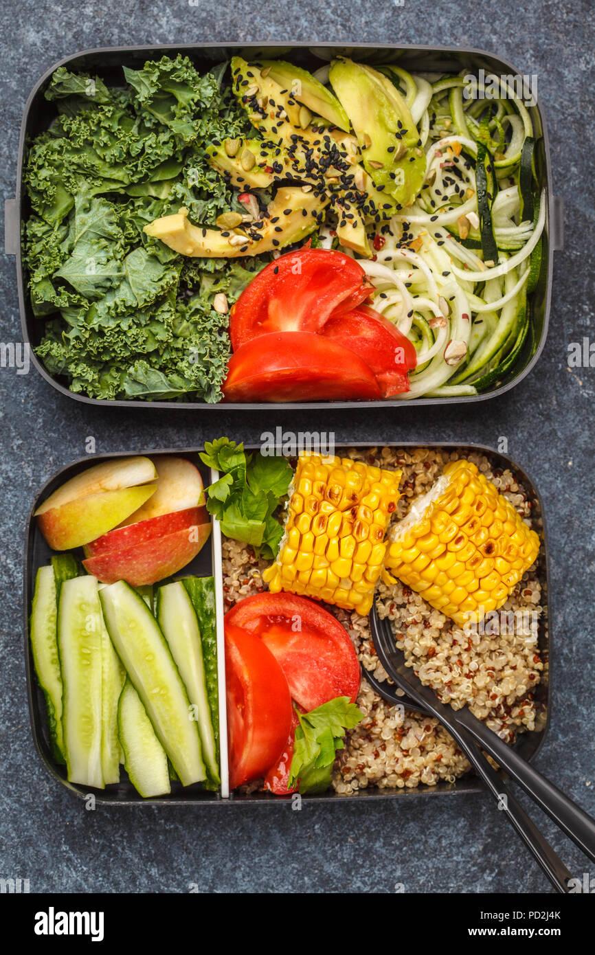 Préparation des repas sains avec des conteneurs le quinoa, l'avocat, le maïs, les courgettes nouilles et le chou frisé. La nourriture à emporter. Fond sombre, vue du dessus. Photo Stock