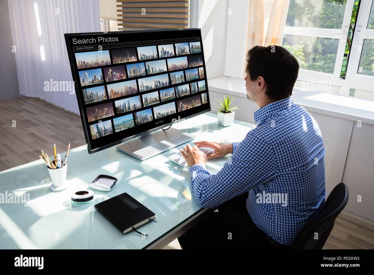 Jeune homme recherche éditeur de photos sur computer in office Photo Stock