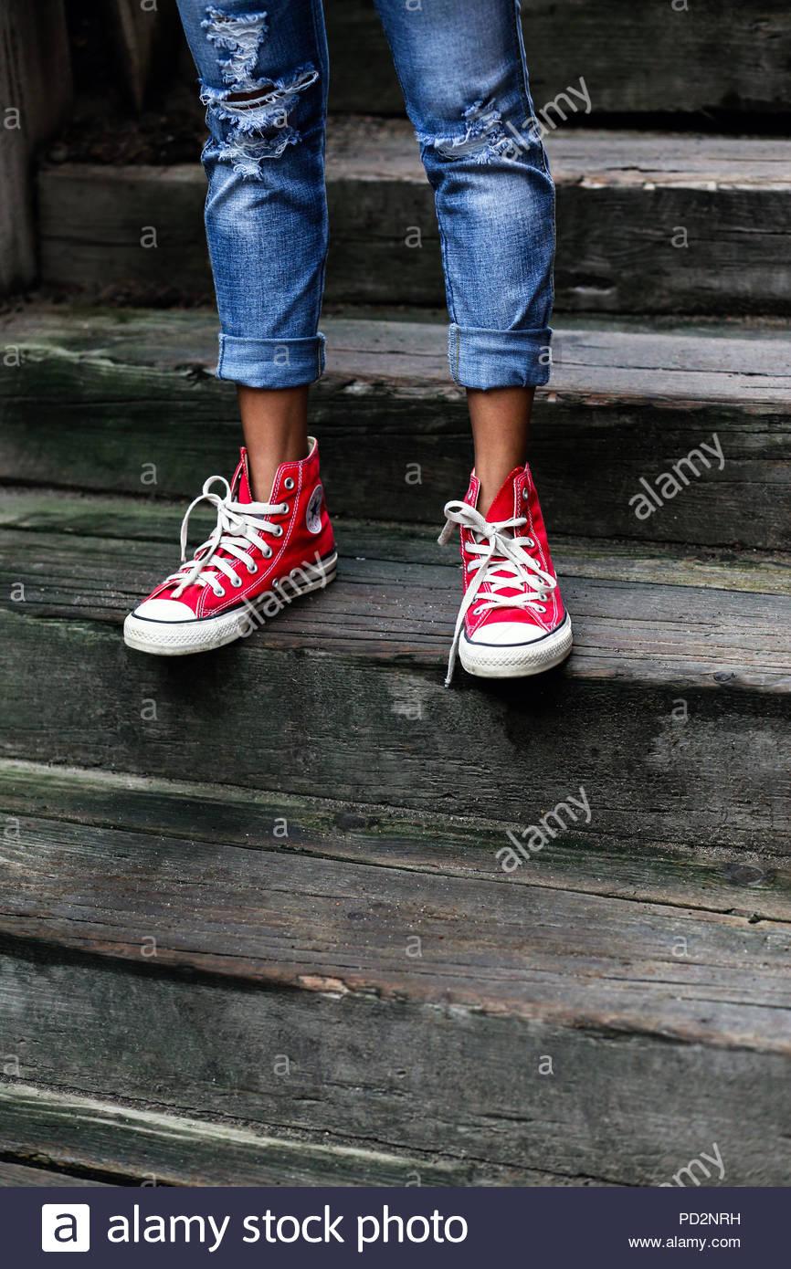 Les jambes et les pieds avec des chaussures Converse rouge