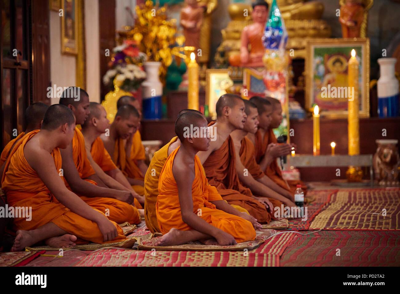 Un groupe de jeunes moines bouddhistes assis sur le sol au cours d'une cérémonie dans l'un des sanctuaires dans leur monastère. À Siem Reap, Cambodge. Photo Stock