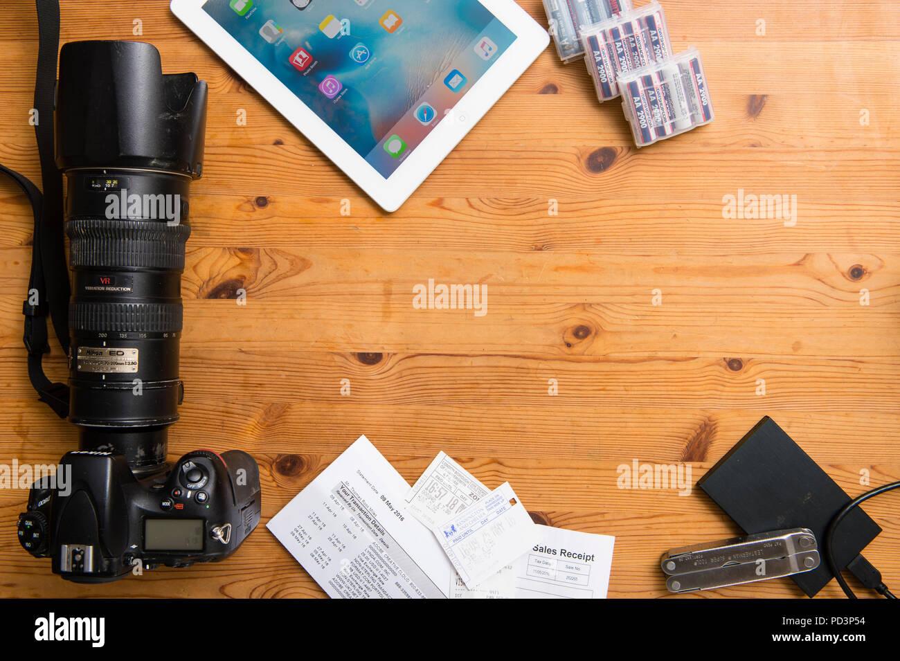 Vue du haut vers le bas de l'équipement de l'appareil photo, l'ipad, les reçus, les batteries Photo Stock