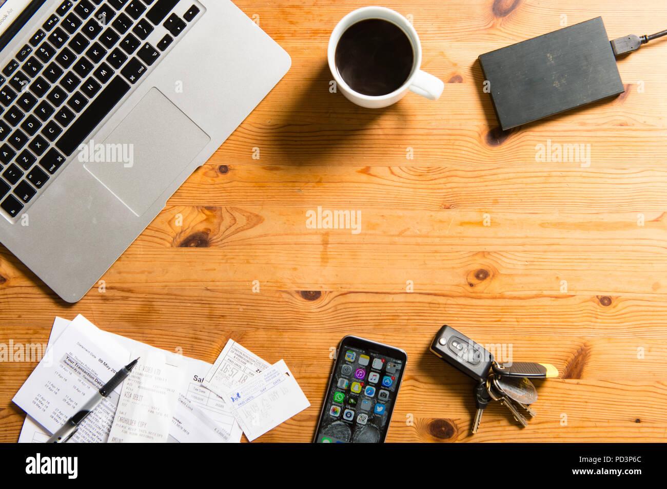 Vue du haut vers le bas du macbook avec du café, les reçus, les clés et l'iphone Photo Stock