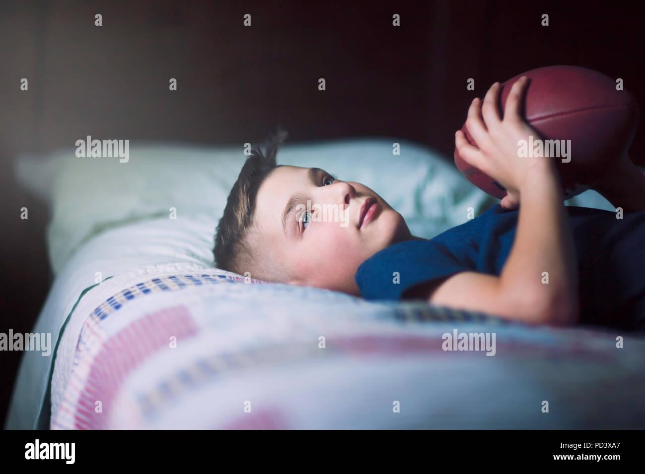 Garçon sur le lit avec le football américain Photo Stock