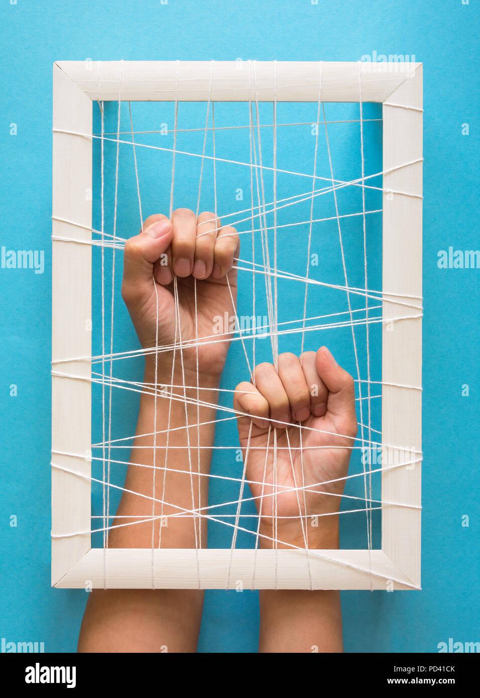 Le concept de santé mentale. Women's Hands essayer de briser les chaînes sur fond bleu Photo Stock