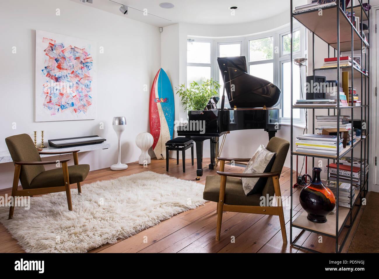 Maison de famille en plan ouvert avec planche de surf, grand piano et paire de fauteuils rétro Photo Stock