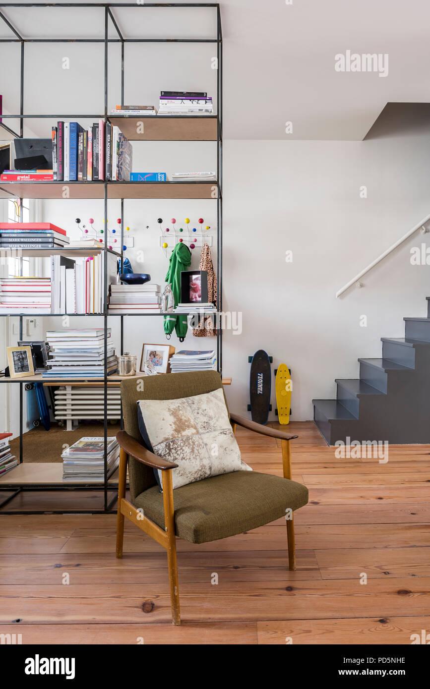 Fauteuil rétro en plan ouvert, espace de vie de famille avec la planche à roulettes et l'unité de rayonnage ouvert Photo Stock