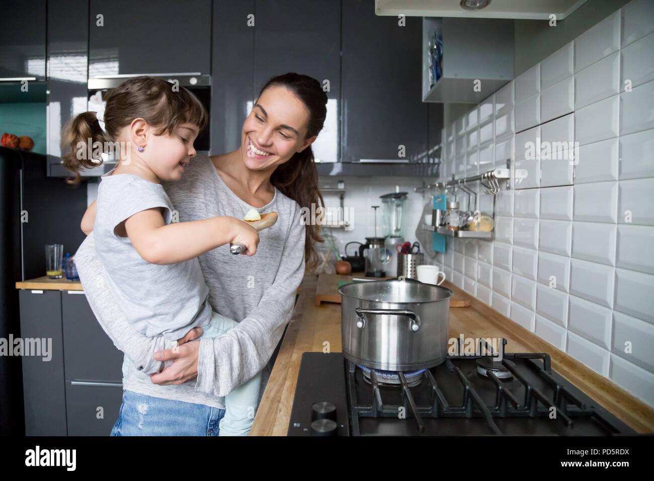 Smiling holding mère fille enfant curieux au sujet de la cuisson en kitche Photo Stock