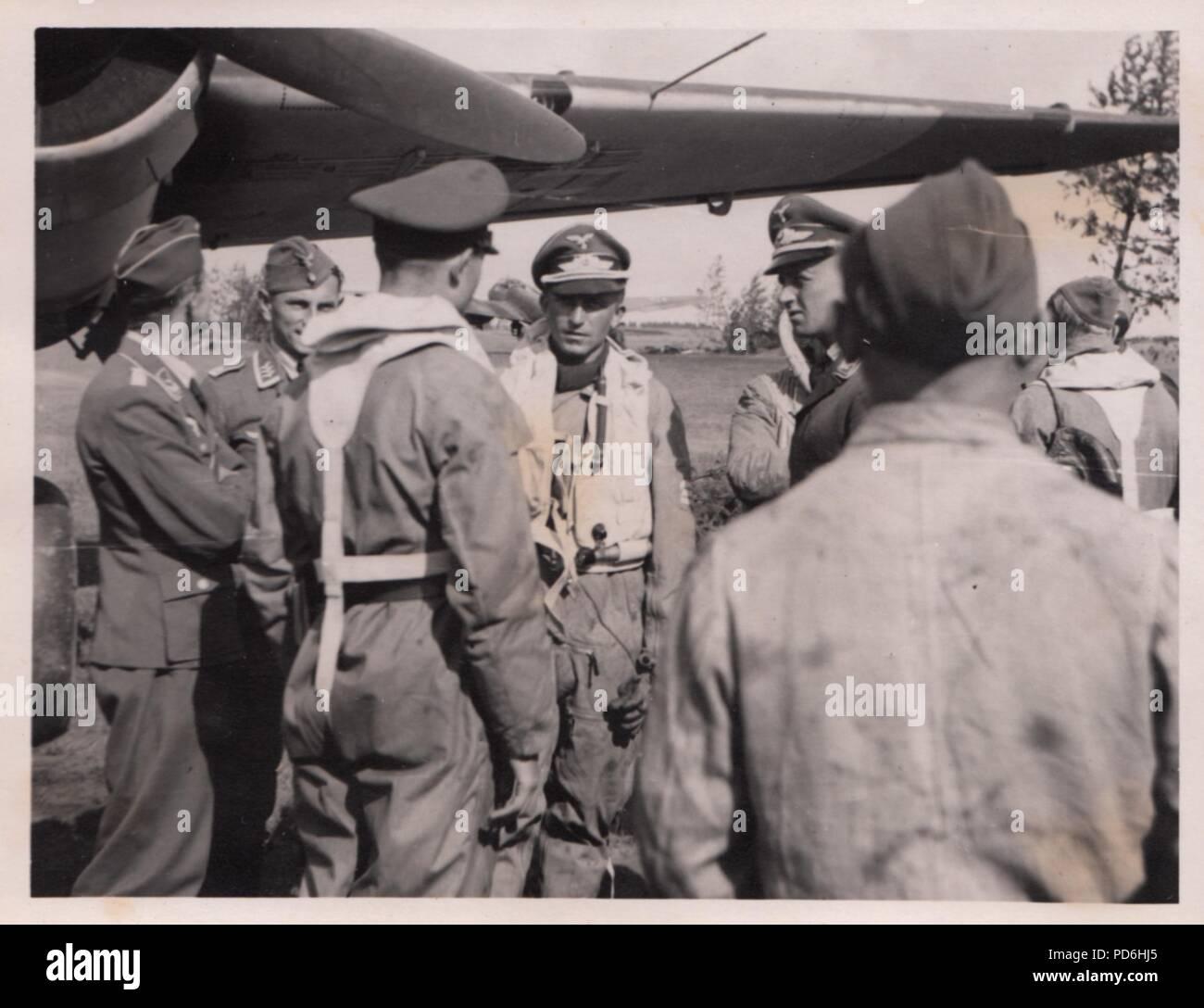Droit de l'album photo de l'Oberleutnant Oscar Müller de la Kampfgeschwader 1: l'Oberleutnant Friedrich Clodius (quatrième à partir de la gauche) en conversation avec l'équipage et le personnel au sol de 5./KG 1 à l'été 1941. Le lieutenant Oscar Müller est sur la gauche avec le dos à la caméra. Clodius est le Staffelkapitän du 5./KG 1 durant l'été 1941 et jusqu'à ce qu'il a été affiché le 8 novembre 1941 manquant. Banque D'Images