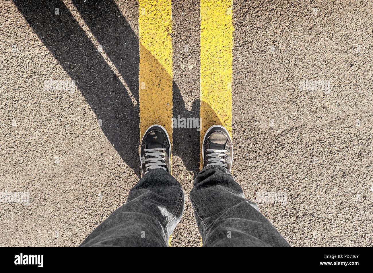 Point de vue personnel de la personne les jambes et s'street lignes jaunes Photo Stock