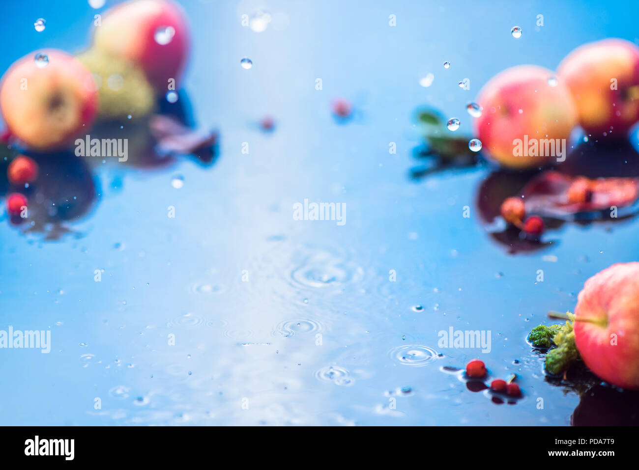 Pluie d'automne cadre avec copie espace. Unfocused les pommes avec les gouttes d'eau et de la place pour le texte. Produits frais et aéré concept la récolte d'automne Photo Stock