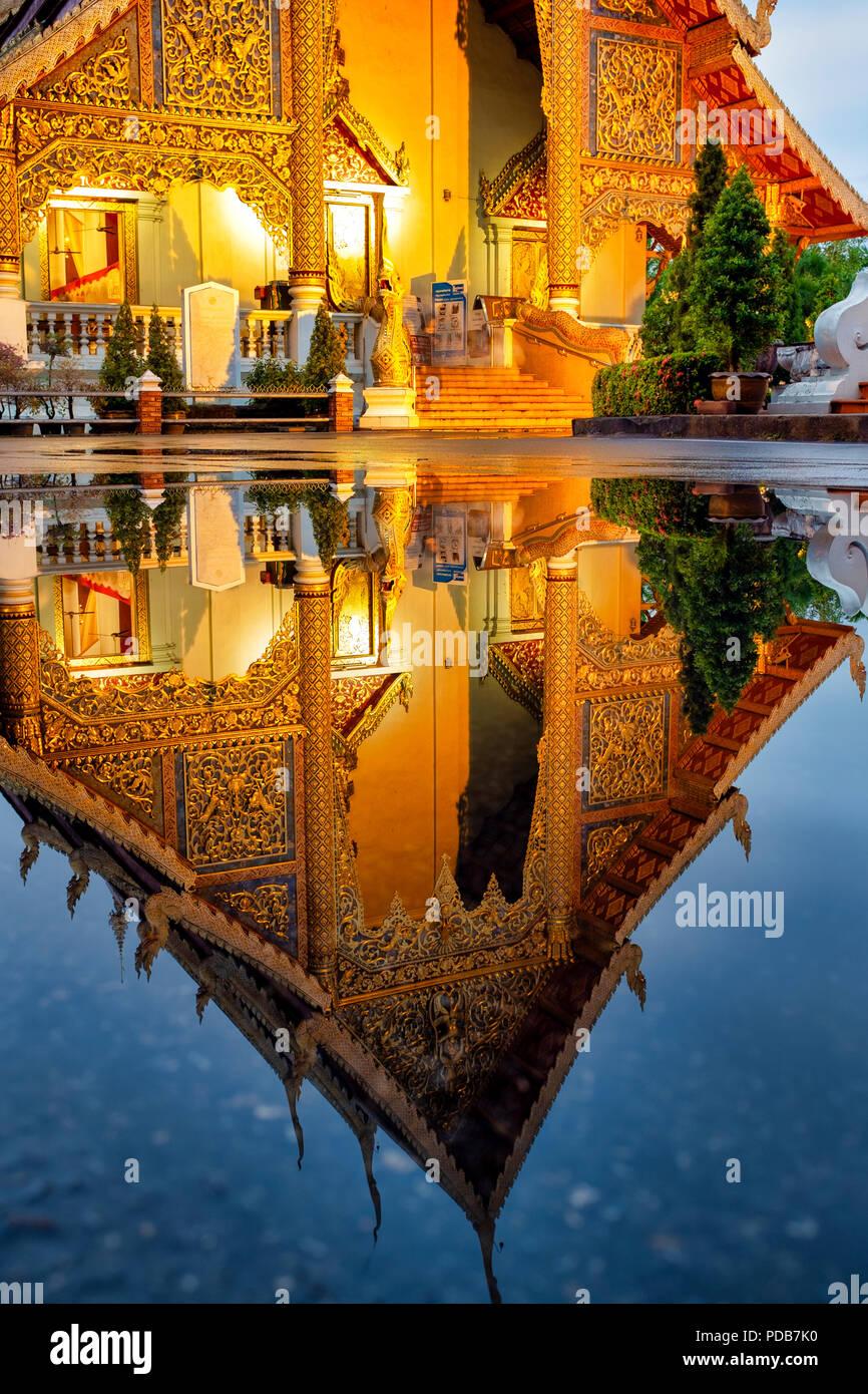 Reflet de la Wihan Luang de Wat Phra Singh dans l'eau d'une flaque, Chiang Mai, Thaïlande Photo Stock