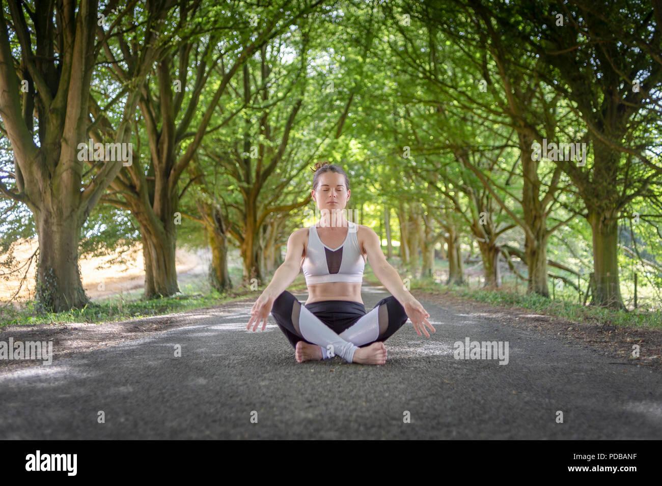 Femme assise méditant à l'extérieur avec des arbres, Photo Stock