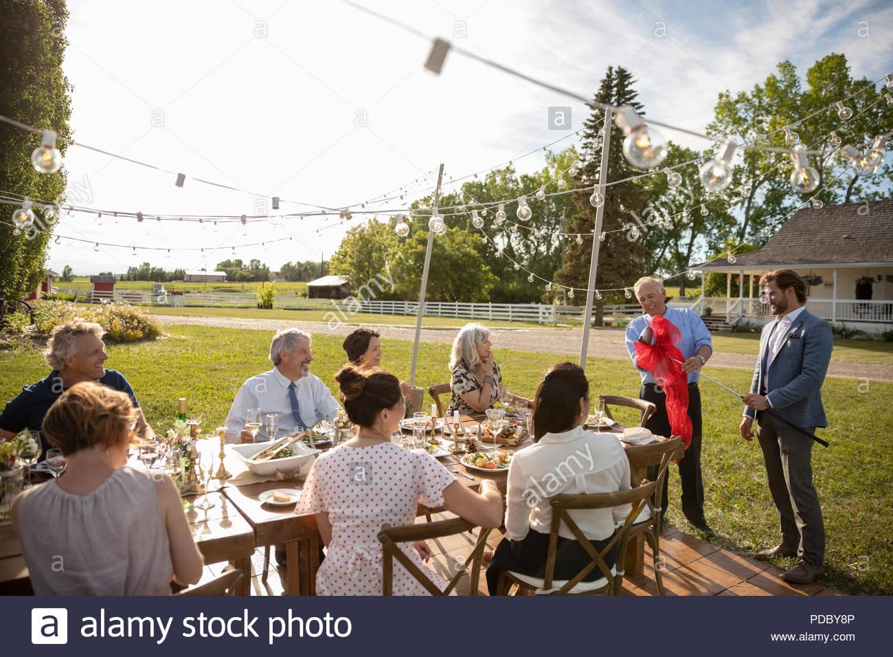 L'observation d'amis donnant fils golf club au père à la retraite partie à sunny jardin rural Photo Stock